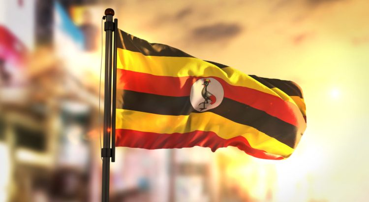 Uganda Flag Against City Blurred Background At Sunrise Backlight 3D Rendering.
