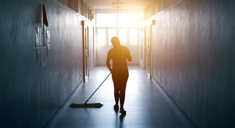 Janitor mopping floor in hallway office building or walkway after school and classroom silhouette work job with sun light background.
