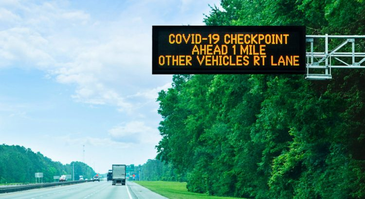 Highway alert: Covid-19 checkpoint ahead, overhead sign in Florida on state border.