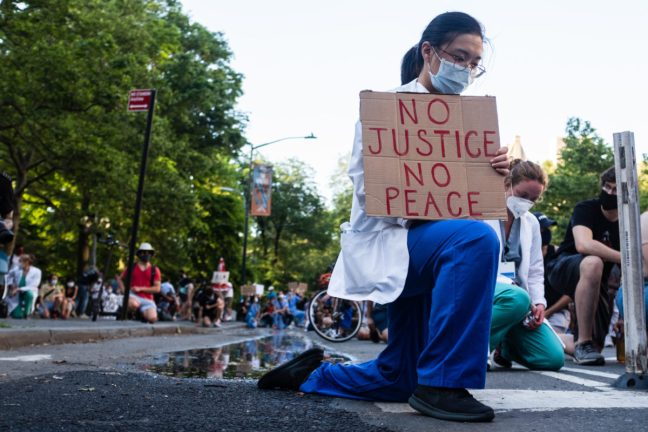 NEW YORK, NEW YORK - JUNE 06, 2020: A health care professional kneels in protest in New York City as part of the movement, 'White Coats for Black Lives,' during the COVID-19 pandemic.
