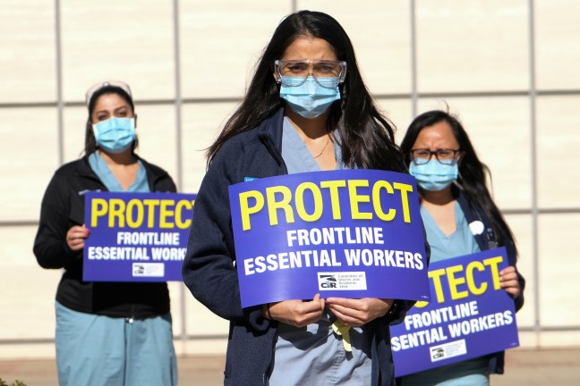 Healthcare workers carrying signs protest for improved Covid-19 testing and workplace safety policies outside of UCLA Medical Center in Los Angeles,Dec. 9, 2020.