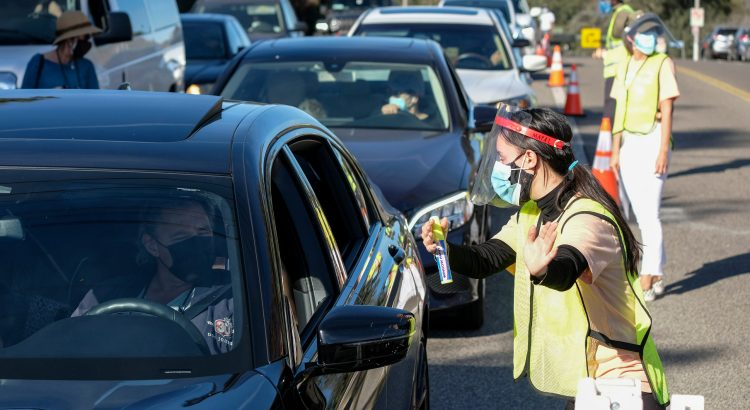 A worker gives directions as motorists wait in lines to get the coronavirus (COVID-19) vaccine in a parking lot at Dodger Stadium, Friday, Jan. 15, 2021, in Los Angeles.