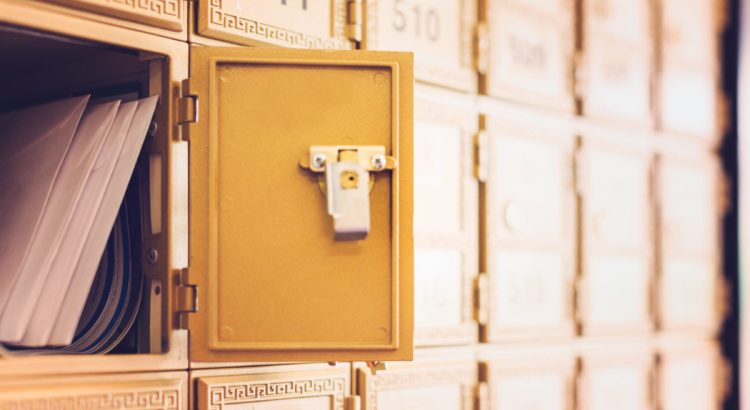 Rows of gold post office boxes with one open mail box.