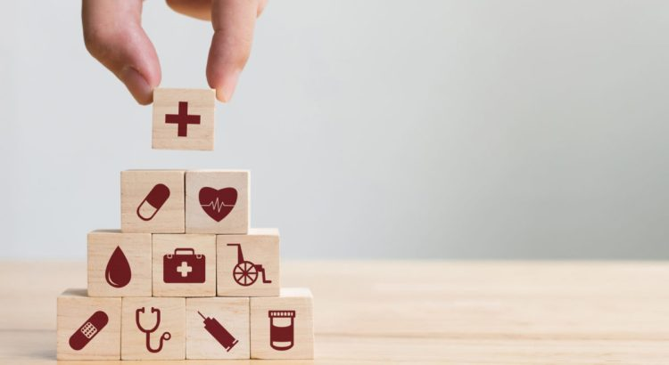 Hand arranging wood block pyramid with health icons on each block.