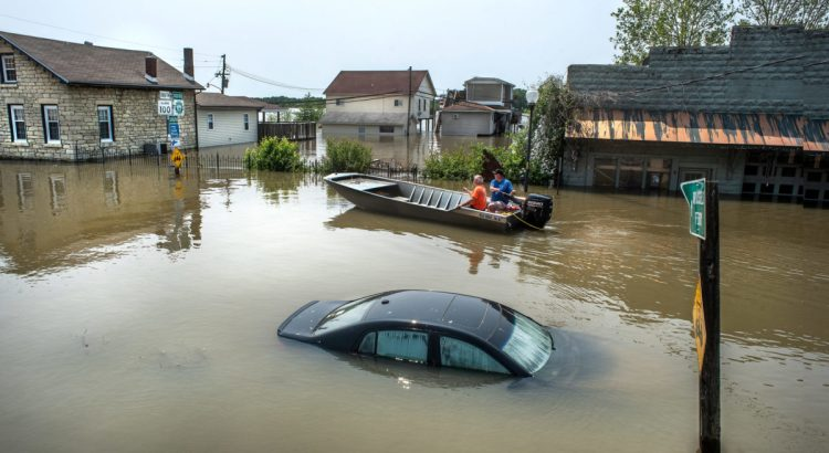 Grafton, Illinois, USA, June 1, 2019 -Car submerged under flood water in small river town, Grafton, Illinois, as Mississippi River floods roads, businesses and houses. vehicle under water, men in boat