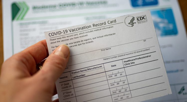 Washington, DC, USA - Closeup view of December, 23, 2020: COVID-19 Vaccination Record Card by CDC on blurred documents background.