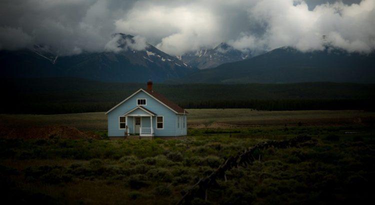 Blue house in grass field.