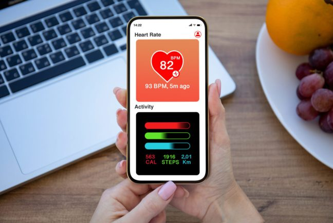 hands hold phone with app heart and activity on screen over table in office