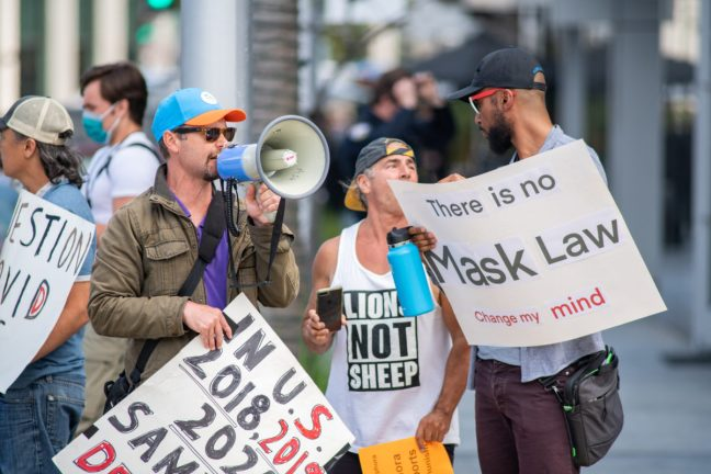 Beverly Hills, CA: April 7, 2021: Anti-mask protesters holding signs related to COVID-19. Beverly Hills and the state of California have a mask mandate requirement.