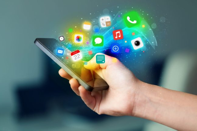Hand holding smartphone with colorful app icons concept.