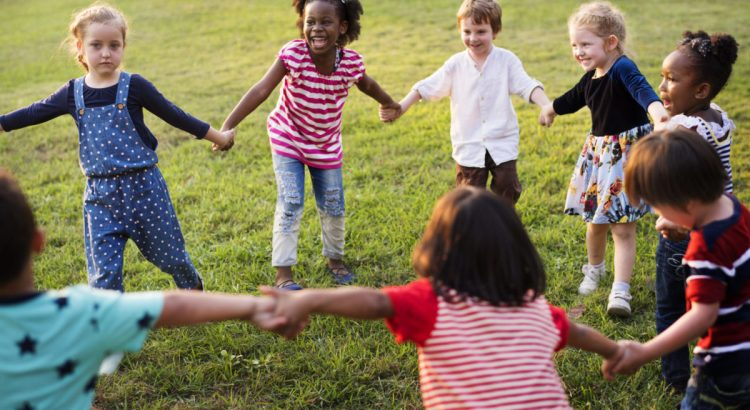 Group of Diverse Kids Playing in a Field Together.