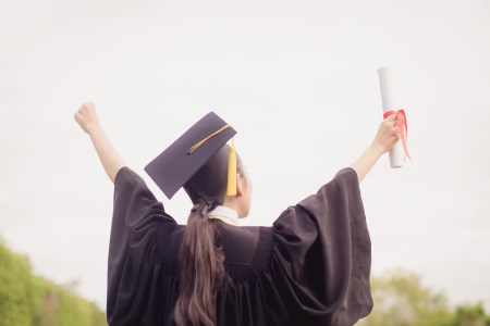 graduate holding up her diploma
