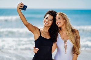 girls taking photos on beach