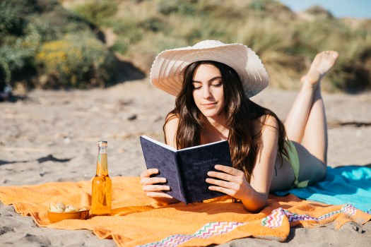 girl reading book at the beach
