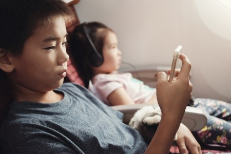 little kids using smart devices on airplane