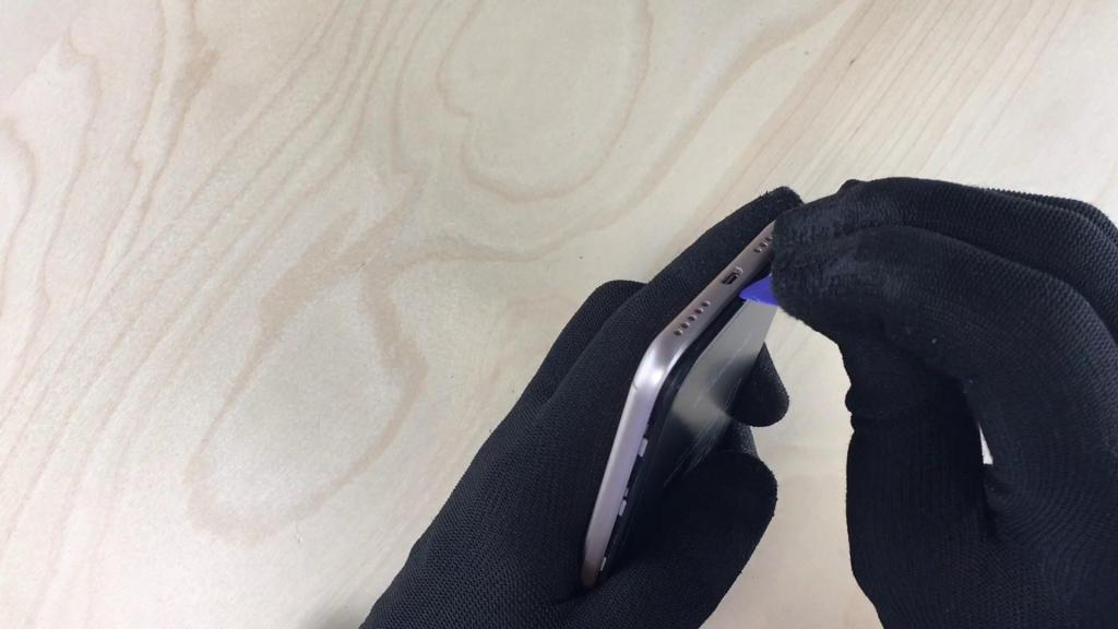 Le technicien enlève la coque arrière pour changer l'écran du Mi A2 Lite avec un médiator.