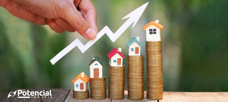 Pilhas de moedas com casas de miniatura no topo, demonstrando crescimento