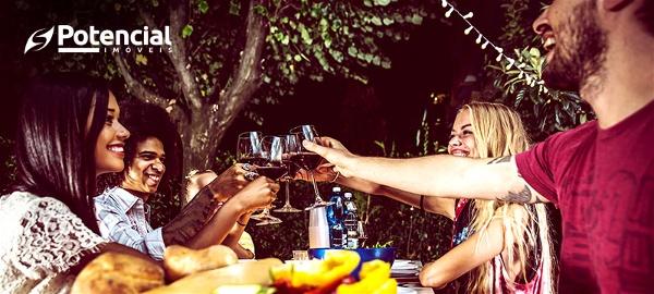 quatro amigos sentados à mesa brindando com vinho