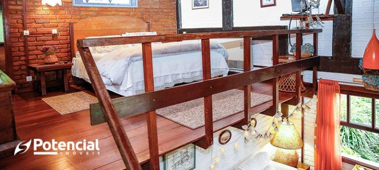 Mezanino Rústico, feito em madeira e com parede de tijolos atrás. No centro dele, a cama de casal fica em destaque