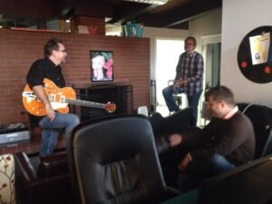 Carson Block, David Puckett and Kevin Wright collaborating at Cohere over a new guitar.