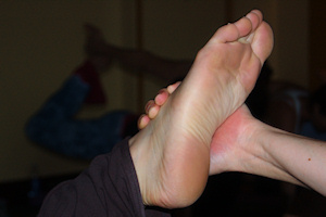 Photo: close-up of hand restrains foot in dancer pose