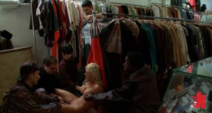 Four men help a submissive girl cum in the back of a clothes' store