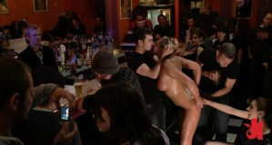 Blonde and naked slut is kissed in a bar by a dominant man while having her hair pulled