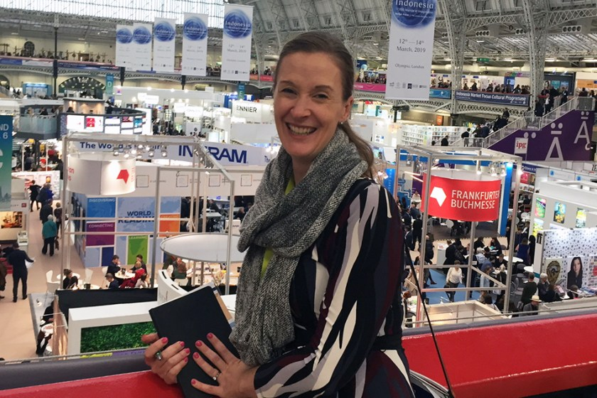 Briana leaning on red balcony overlooking the London Book Fair
