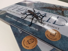 Am artful stack of Phasmid picture books, with a figurine of a Lord Howe Island Stick Insect standing on top.