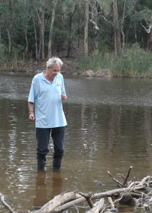 Michael Tyler in gumboots standing in the shallows of a bushland lake