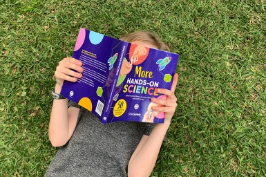 A young child lying on their back on grass reading More Hands-On Science. Their face is obscured by the book.