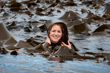 Photo of Ceridwen Fraser in the ocean immersed up to her neck, surrounded by a multitude of large, dark green strands of kelp. She is smiling and draping one of the flat, wide kelp strands over her head.
