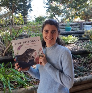 Author Penny Jaye smiling and holding a copy of her book One Potoroo