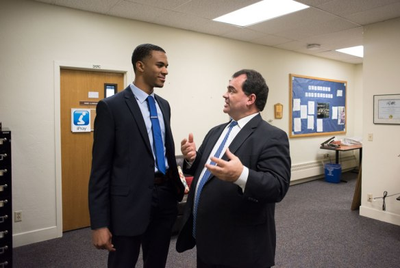 Recent business graduate Michael Lawrence talks with Dr. John Nunes in the department of business.