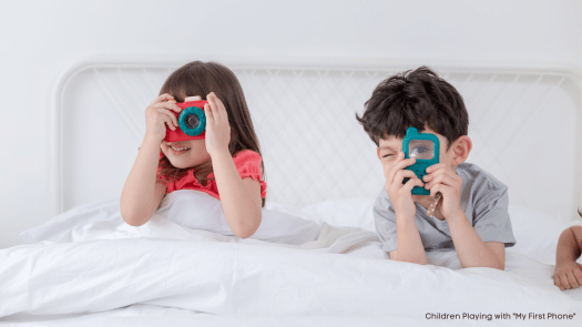 Two young kids playing pretend with phones