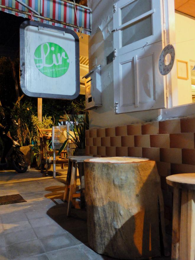 Beranda depan Lir, didominasi meja-kursi kayu, signage kayu, dan kotak surat di dinding.