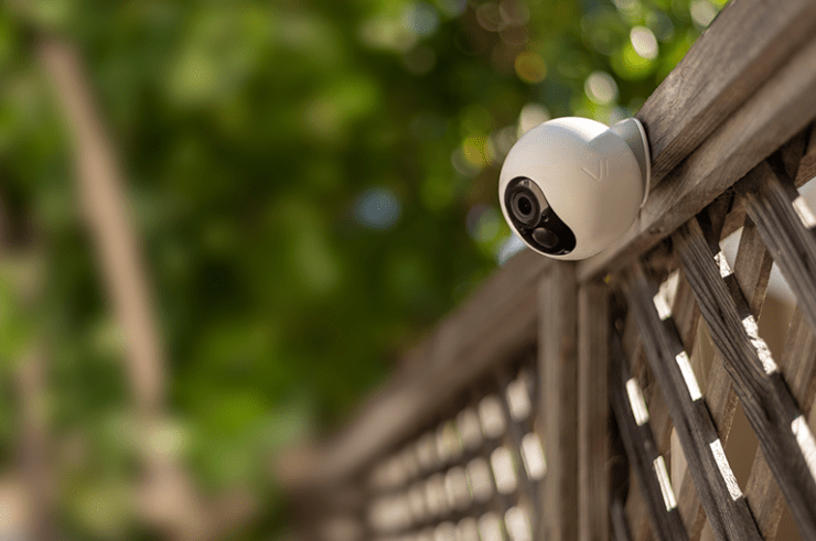 The VAVA Home Cam sits on a fence in garden to watch for any intruders
