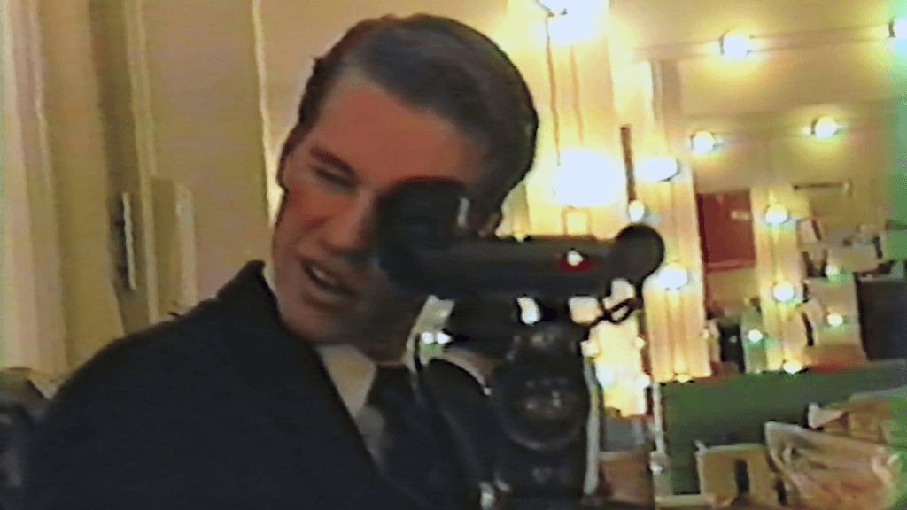 Val Kilmer pointing a large video camera at the screen