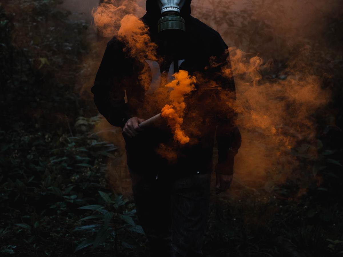 man in gas mask spraying chemicals