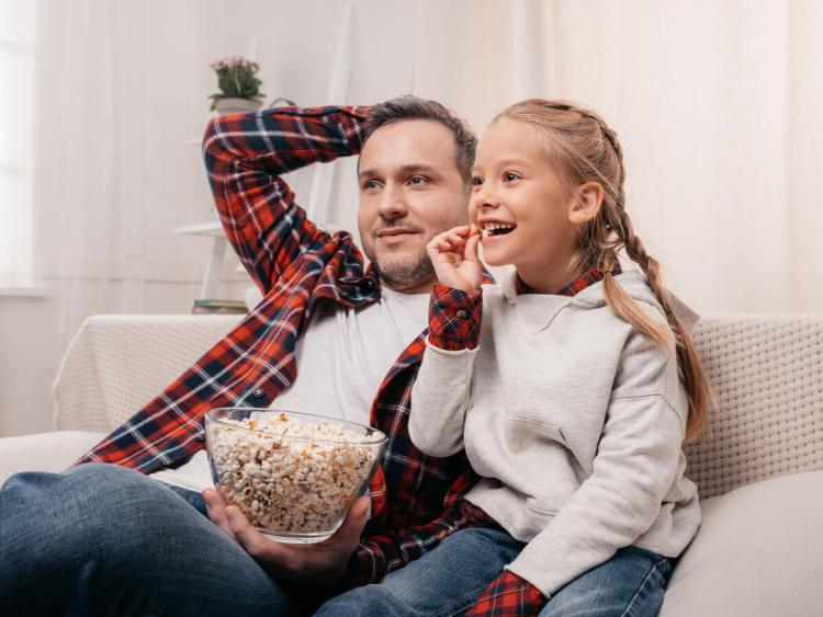 Father and daughter eating popcorn on couch and watching tv