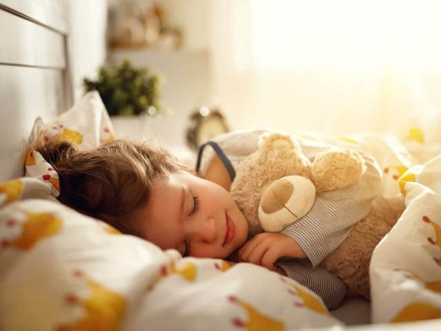 Young girl sleeping with teddy bear, with morning light streaming in behind her