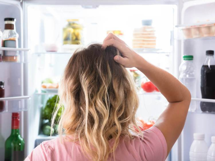 Woman scratching head and looking for something in her french door refrigerator