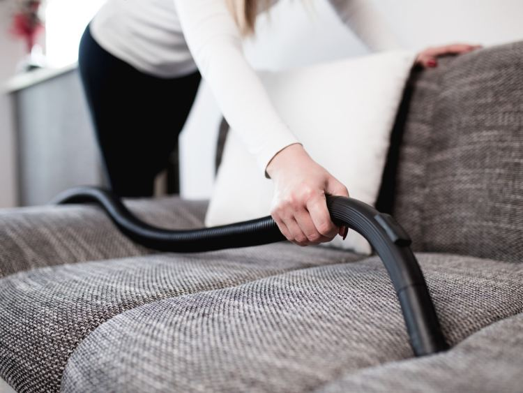 Woman leans over gray couch using vacuum attachment to clean between cushions