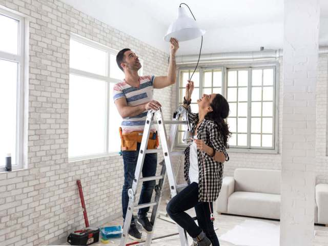 Couple in new home replacing a light fixture