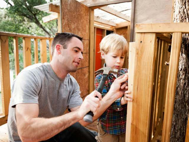 Father and son using hammer and nails to build a wooden kids fort