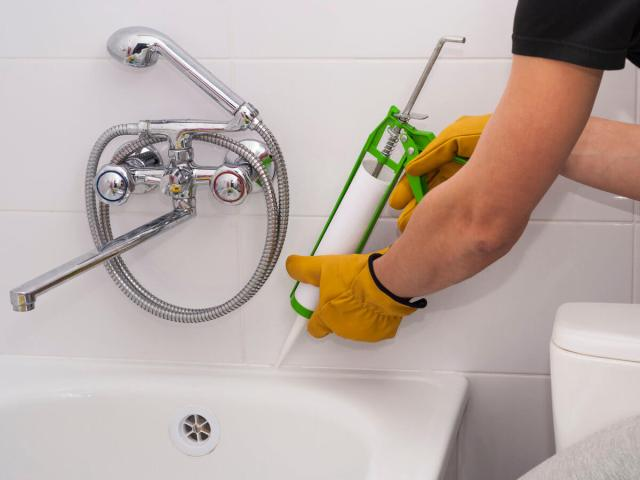 Wearing gloves to re-caulk and re-grout shower bath tub