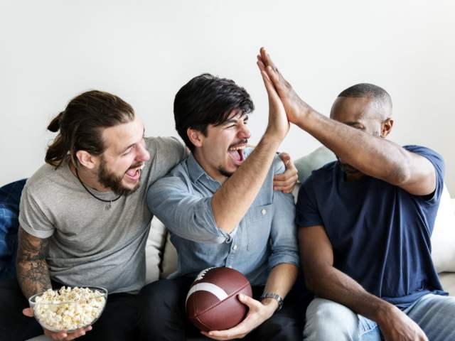 Three friends watching a football party