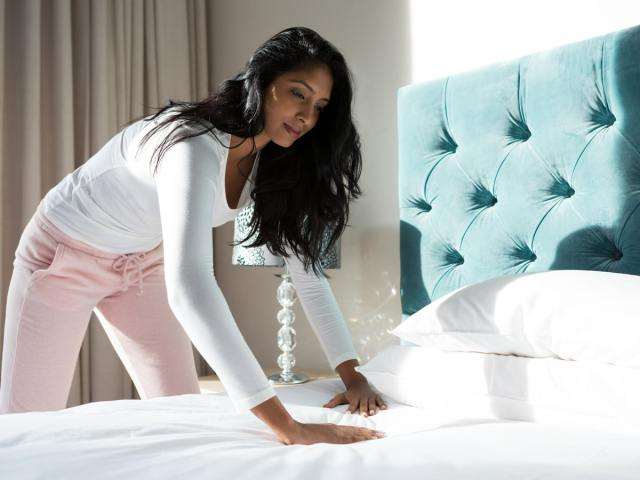 Woman smoothing out new bedsheets