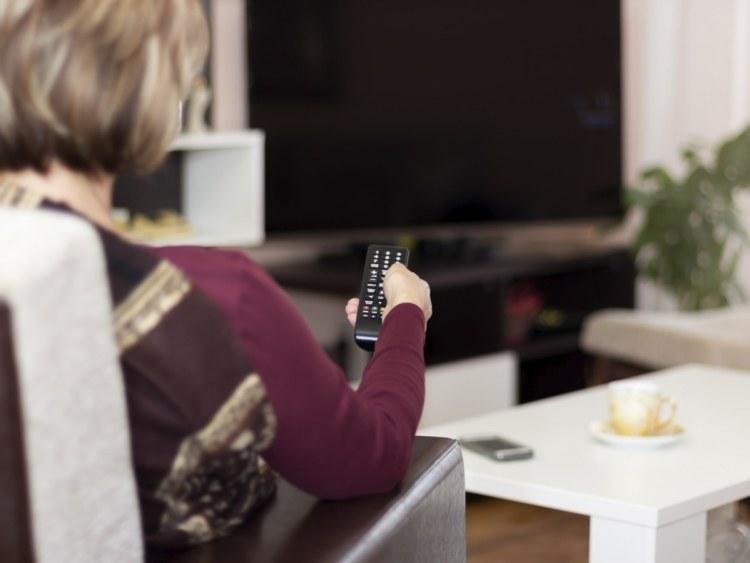 Woman turning on TV