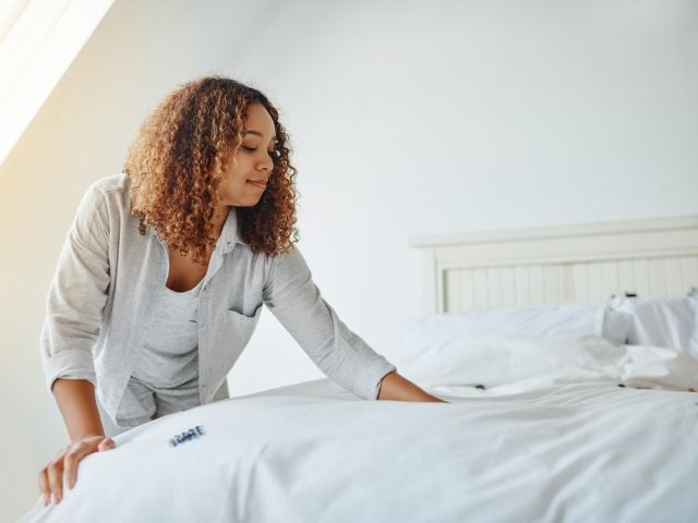 Woman smoothing out a made bed